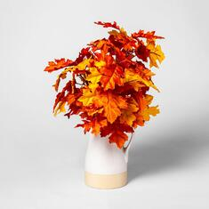 Cream colored vase with fall leaves bouquet