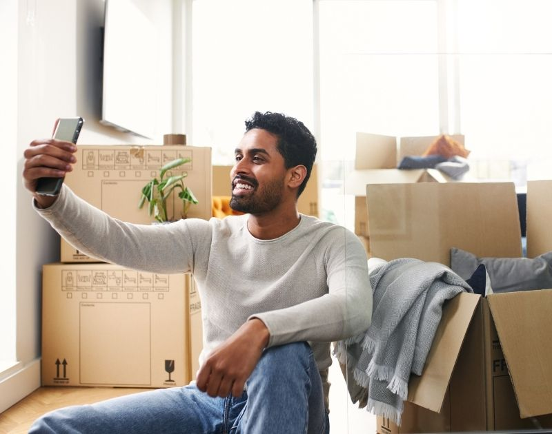 Housing Image- Guy takes a selfie while unpacking moving boxes