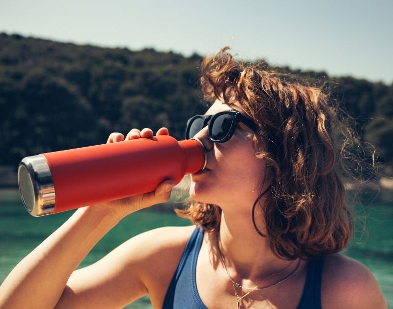 Sustainability Image- Women drinks out of a red water bottle.