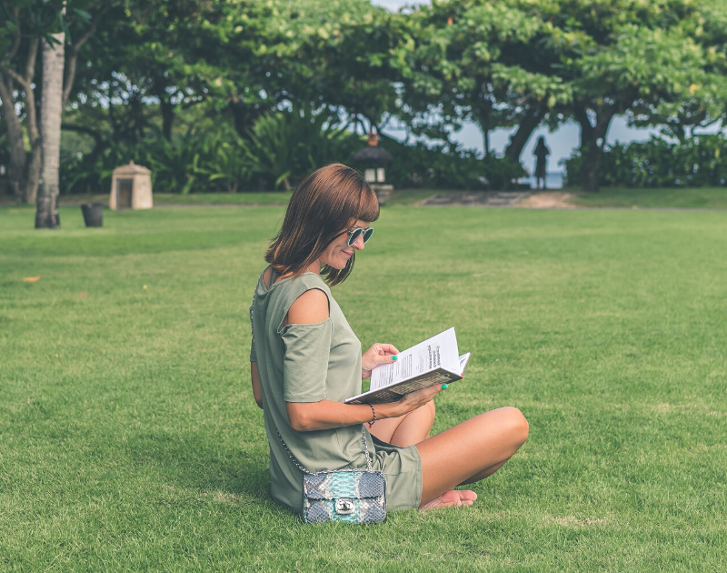 A young woman reading outside at a park