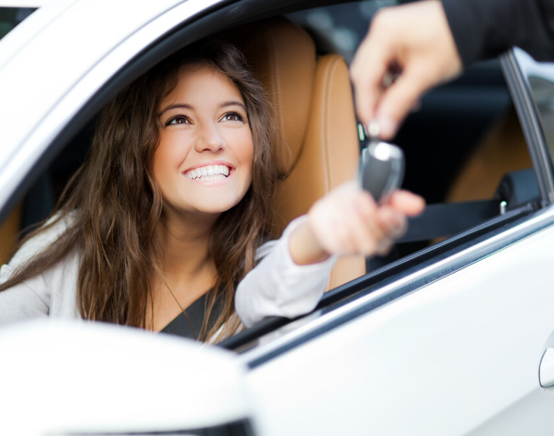 Young woman sitting in car and smiling while being handed her new car keys