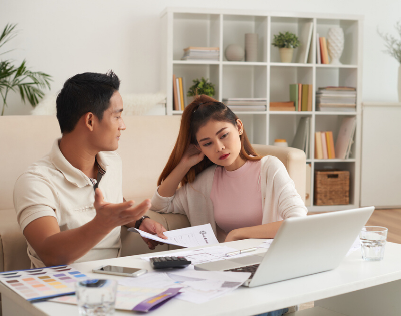 Young couple discussing finances and becoming frustrated