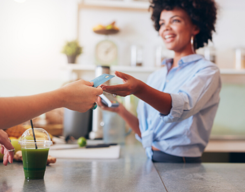 woman accepting credit card for drink purchase