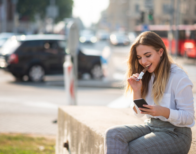 woman snacking and looking at cell phone